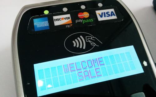 A payment terminal with an NFC payment logo compatible with Apple Pay and Google Wallet
