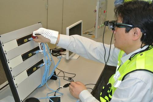 A Fujitsu Laboratories staffer demonstrates a glove-like wearable technology prototype that has a near field communication tag reader and gestural sensors. It works with a head-mounted display to speed up maintenance tasks such as cabling.