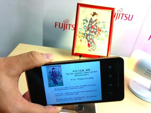 A smartphone shows information downloaded fom a cloud sever after its camera picked up ID information in LED light reflected off a print by ukiyo-e woodblock artist Utagawa Hiroshige during a demo by Fujitsu Laboratories in Tokyo on Monday.