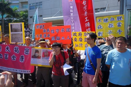 Protesters assemble outside Foxconn headquarters in Taipei on June 25, 2015.