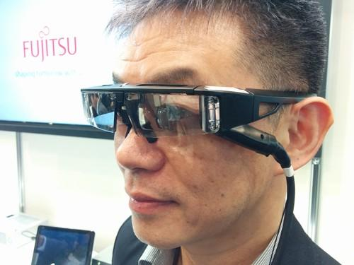 Mitsuru Sugawara, CEO of QD Laser, shows off prototype smartglasses in Tokyo on Tuesday. The glasses house a small laser projector that projects imagery from a front-facing camera or a mobile device onto a user's retina. The glasses could help people with vision loss.