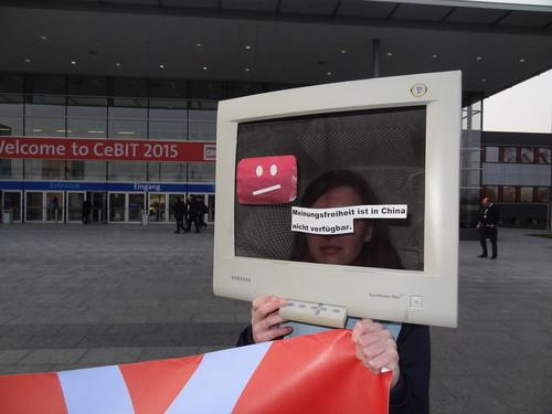 """A protestor disguised as a computer at the entrance to Cebit 2015 displays an error message: """"In China, freedom of speech is not available."""""""
