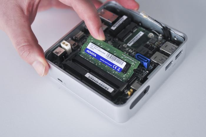 Memory slots in at an angle; push it down until it clips into place.